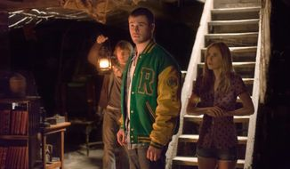 "Fran Kranz, Chris Hemsworth and Anna Hutchison (from left) check out the creepy basement of the home they've entered in ""The Cabin in the Woods."" (Lionsgate via Associated Press)"
