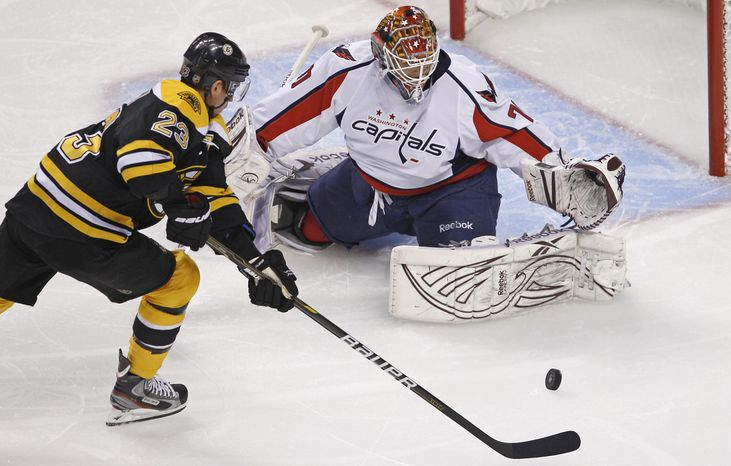 Boston Bruins center Chris Kelly (23) shoots as Washington Capitals goalie Braden Holtby (70) makes the save during the first period of Game 1 of an NHL hockey Stanley Cup first-round playoff series in Boston, Thursday, April 12, 2012. (AP Photo/Charles Krupa)