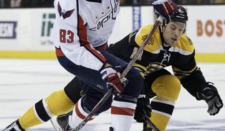 Washington Capitals center Jay Beagle attempts to get a shot off against the defense of Boston Bruins center Gregory Campbell during the first period of Game 1 of the first-round playoff series in Boston on Thursday, April 12, 2012. (AP Photo/Elise Amendola)