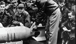 "U.S. Army Air Corps Maj. Gen. James H. ""Jimmy"" Doolittle fastens a medal on the tail of a 500-pound bomb that his raiders dropped on Tokyo on April 18, 1942. Eighty men in 16 planes surprised the Japanese and shattered their sense of being impregnable. (Associated Press)"