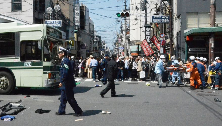 Rescue workers carry an injured person after a car went amok April 12, 2012, in the Gion district of Kyoto, Japan, which was crowded with tourists and cherry blossom viewers. More than a dozen pedestrians were injured, some critically. (Associated Press)