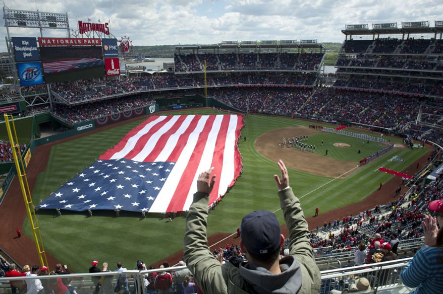 The American flag is unfurled in the outfield as the Washington Nationals host the Cincinnati Reds during the Nationals' home opener, in Washington, D.C., Thursday, April 12, 2012. (Rod Lamkey Jr/The Washington Times)
