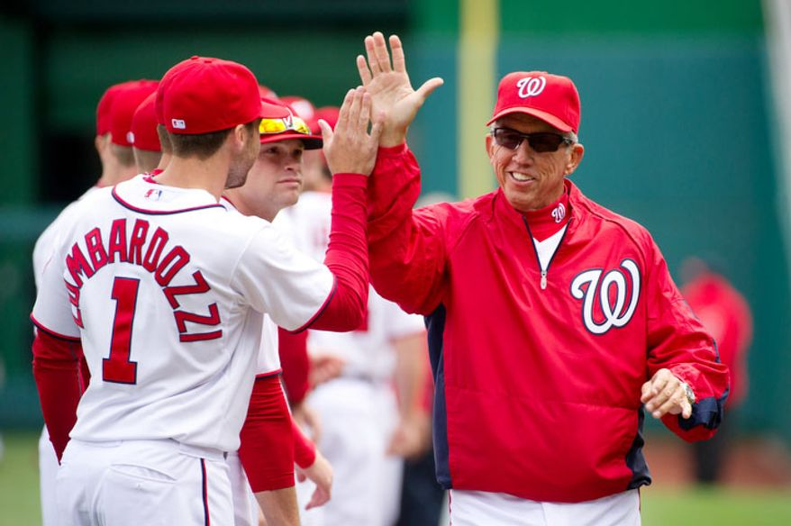 Washington Nationals second baseman Stephen Lombardozzi (1), left, high fives Washington Nationals manager Davey Johnson (5), right, before the Washington Nationals take on the Cincinnati Reds in their home opener. (Andrew Harnik/The Washington Times)
