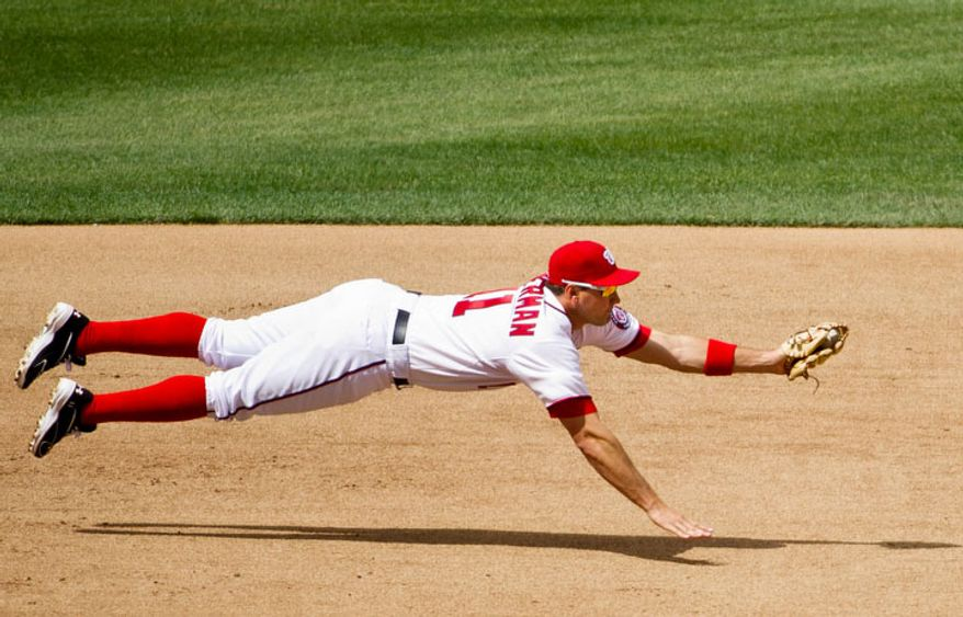 Washington Nationals third baseman Ryan Zimmerman (11) makes a catch on a ball hit by Cincinnati Reds left fielder Ryan Ludwick (48) in the fifth inning. (Andrew Harnik/The Washington Times)
