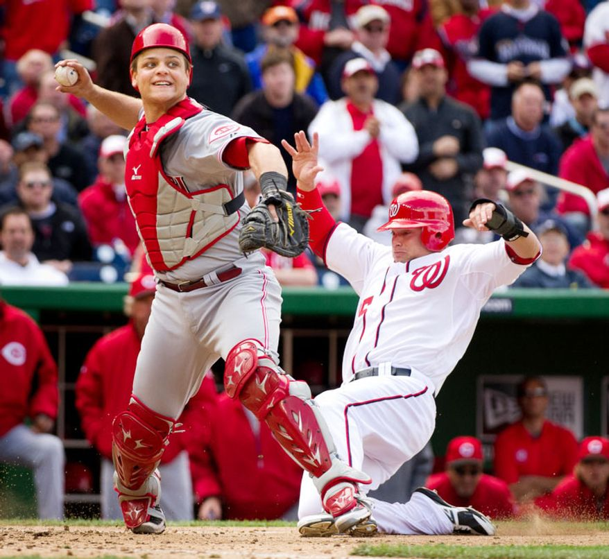Washington Nationals center fielder Brett Carroll (15) slides into home plate too late as Cincinnati Reds catcher Devin Mesoraco (39), left, throws to first on a double play at the bottom of the ninth inning to send the game into extra innings. (Andrew Harnik/The Washington Times)