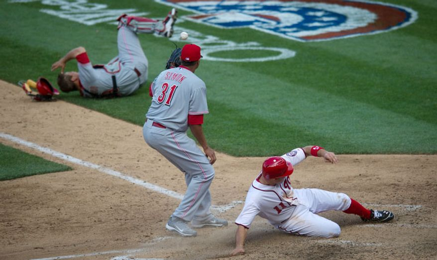 Cincinnati Reds pitcher Alfredo Simon (31) and catcher Devin Mesoraco (39) can't make the tag as Washington Nationals third baseman Ryan Zimmerman (11) scores the winning run on a wild pitch by Alfredo Simon in the bottom of the 10th inning. (Rod Lamkey Jr/The Washington Times)