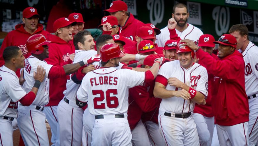 Washington Nationals third baseman Ryan Zimmerman (11) is mobbed by his teammates after scoring the winning run on a wild pitch in the bottom of the 10th inning. (Rod Lamkey Jr/The Washington Times)