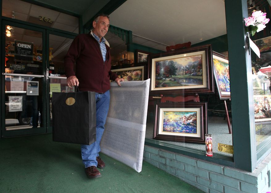 Tom Cuquet leaves the Thomas Kindade Gallery after purchasing several of the artist's works in Kinkade's boyhood hometown of Placerville, Calif., Monday, April 9, 2012. (AP Photo/Rich Pedroncelli)