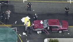 **FILE** Police officers and investigators stand around a car that plowed through a crowded farmers market in Santa Monica, Calif., on July 16, 2003. The body of one of the victims is seen covered at left. (Associated Press)