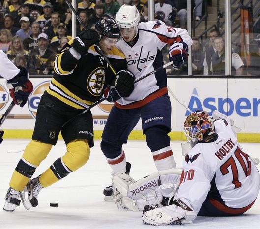 Washington Capitals defenseman John Carlson keeps Boston Bruins center David Krjejci away from the loose puck. The Capitals used their bodies to block shots and clear the crease area during their 1-0 overtime loss in Game 1 of