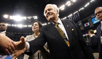 FILE - This Jan. 1, 2012 file photo shows New Orleans Saints owner Tom Benson and his wife Gayle Benson shaking hands before an NFL football game against the Carolina Panthers in New Orleans. A person familiar with the deal says the NBA has agreed to sell the New Orleans Hornets to Saints owner Tom Benson for $338 million. The person spoke to The Associated Press Friday, April 13, 2012, on condition of anonymity because the deal has not been announced. (AP Photo/Bill Haber, File)