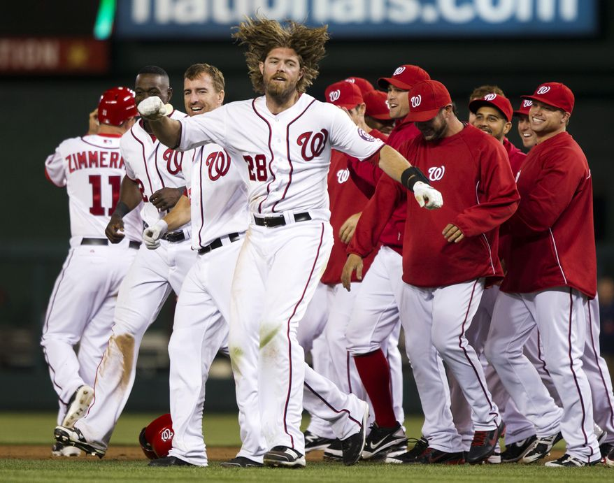 Washington Nationals right fielder Jayson Werth (28) escapes from his teammates after being mobbed for hitting the game-winning single during the 13th inning against the Cincinnati Reds on Friday, April 13, 2012, in Washington. The Nationals won 2-1. (AP Photo/Evan Vucci)