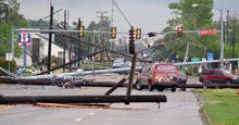 Downed power lines litter 24th Avenue Southwest at the Lindsey Street intersection after a tornado hit Friday afternoon April 13, 2012, in Norman, Okla. (AP Photo/The Norman Transcript, Kyle Phillips)