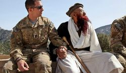 Army Capt. Mark Moretti meets with a village elder before his unit leaves an outpost in the Korengal Valley of Afghanistan. During a shift in tactics, U.S. forces gave up a network of hilltop platoon outposts in favor of a more mobile engagement of the Taliban. (Department of Defense)
