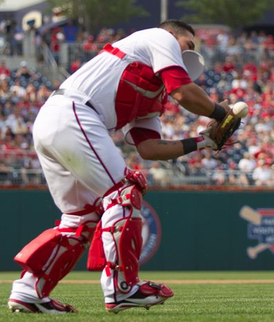 Nationals catcher Wilson Ramos can't put the squeeze on Reds pitcher Mike Leake's sacrifice bunt attempt in the seventh. Leake was thrown out by third baseman Ryan Zimmerman. (Associated Press)