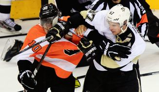Pittsburgh captain Sidney Crosby (right) shoves his glove and stick into the face of Philadelphia center Brayden Schenn as several fights break out during the third period. (Associated Press)