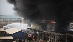 Firefighters use water canons against a blaze in the storage facilities of an oil company in Suez, Egypt, on Sunday, April 15, 2012. One person died and dozens were injured in the fire, which raged for nearly 20 hours, the local police chief said. (AP Photo/Khalil Hamra)