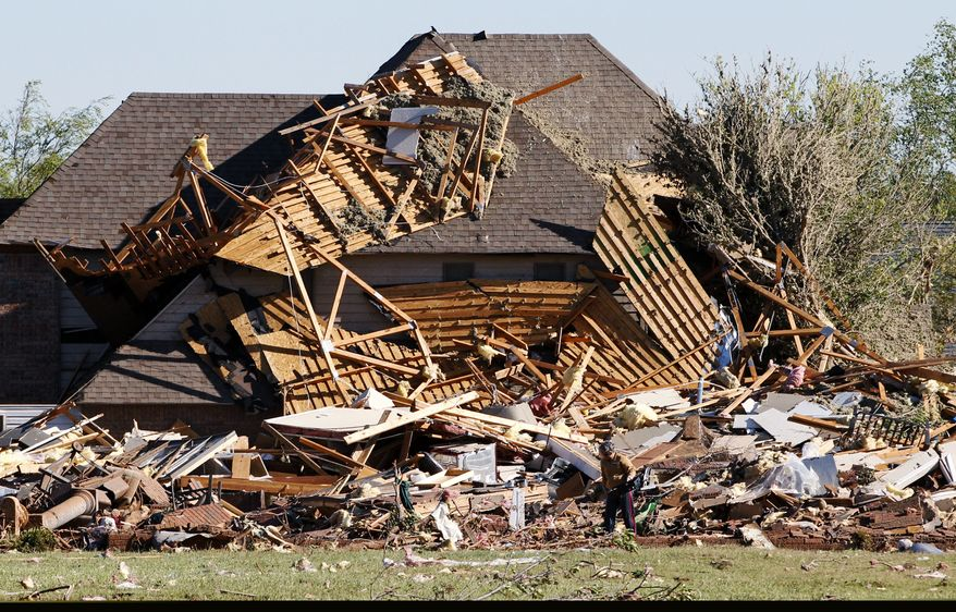 Sue Lord is dwarfed by the debris from her home, which is piled up on her neighbor's home, following a tornado in Woodward, Okla., on Sunday, April 15, 2012. Ms. Lord was in the home when the tornado struck but was not injured. (AP Photo/Sue Ogrocki)