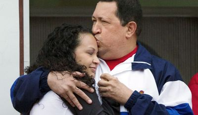 """Mr. Chavez kisses the forehead of his daughter, Rosa Virginia, at the presidential palace in Caracas. The socialist president said that he has faith in a """"miracle,"""" as he undergoes radiation therapy in Cuba following two surgeries to remove pelvic tumors."""