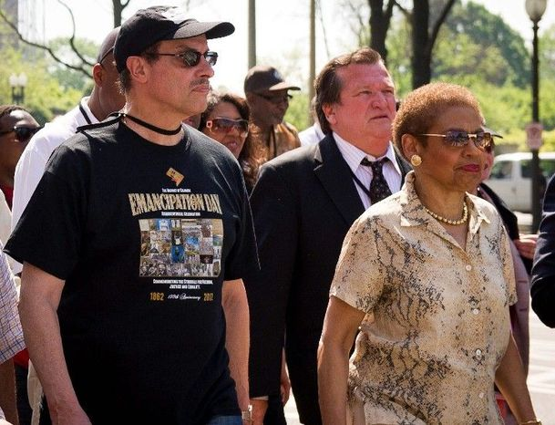Delegate Eleanor Holmes Norton, the District's nonvoting member of Congress, is joined by Mayor Vincent C. Gray as they march in the city's Emancipation Day parade Monday. The celebrated day in 1862 was about nine months before the historic Emanicpation Proclamation. (Rod Lamkey Jr./The Washington Times)