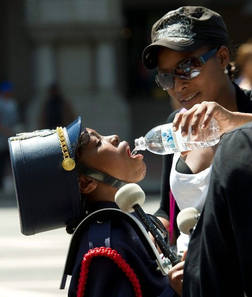 Caprice Casson offers water to Dana Treece, 10, a drummer in the J.C. Nalle Elementary School band, as they make they way along Pennsylvania Avenue during the District of Columbia Emancipation Day 2012 Parade on Monday, celebrating the 150th anniversary of slaves being freed in the District on April 16, 1862, by President Abraham Lincoln. (Rod Lamkey Jr./The Washington Times)