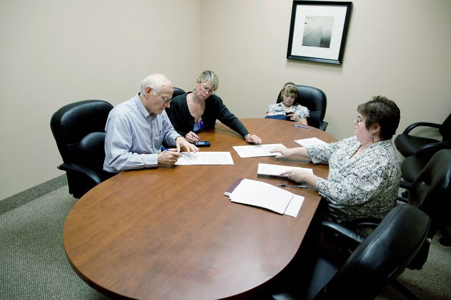 Bill and Kelly Noorish (above) bring along 12-year-old Nyomie as they sign papers with escrow assistant Deb Arebalo. The Noorishes will be moving with their 32-year-old son and his wife into a Las Vegas home like the one shown by Joy Broddle (below). (Associated Press)