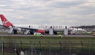 A Virgin Atlantic Airbus A330, originally bound for Orlando, Fla., sits on the runway at Gatwick Airport outside London after it made an a full emergency landing. (AP Photo/Lorna Willson, Press Association)