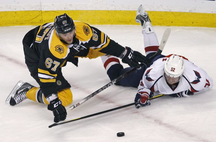 Washington Capitals defenseman Mike Green (right) tries to get a stick on the puck after being dropped to the ice by Boston Bruins left wing Benoit Pouliot during the third period of the Capitals' 2-1 victory in Game 2 of their first-round playoff series in Boston on April