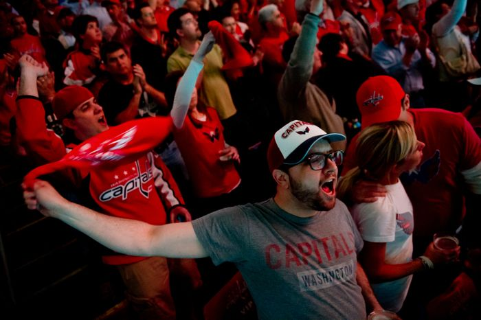 Paul Bonsiero, center bottom, waves a red towel as he and other fans cheer before the Washington Capitals take on the Boston Bruins in game three of National Hockey League first round playoff hockey at the Verizon Center, Washington, D.C., Monday, April 16, 2012. (Andrew Harnik/