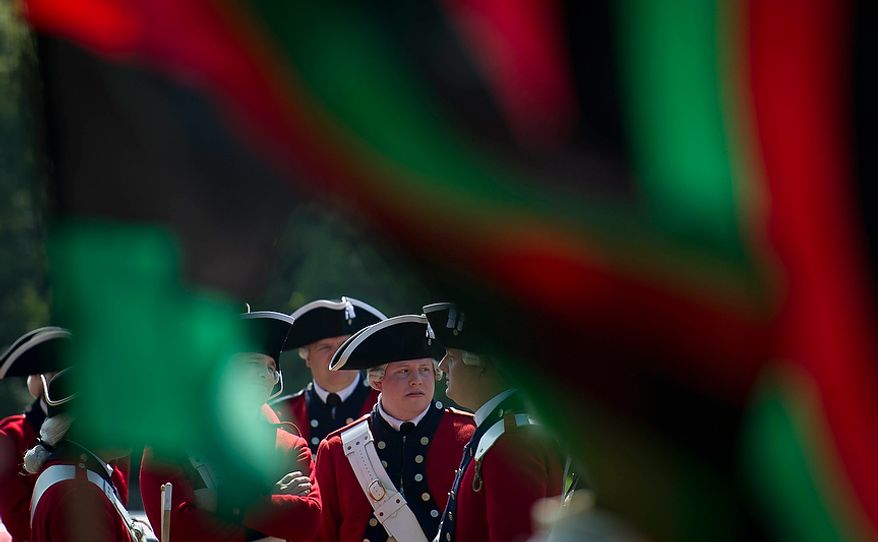 Members of the 3rd U.S. Infantry Old Guard Fife and Drum Corps are seen through the colors of an African flag as they wait to march in the District of Columbia Emancipation Day 2012 parade in Washington, D.C., Monday, April 16, 2012., celebrating the150th anniversary of the District of Columbia Emancipation Act. 150 ears ago, on April 16, 1862, President Abraham Lincoln signed a bill ending slavery in the District of Columbia. Passage of this law came 8 1/2 months before President Lincoln signed his Emancipation Proclamation. (Rod Lamkey Jr/The Washington Times)