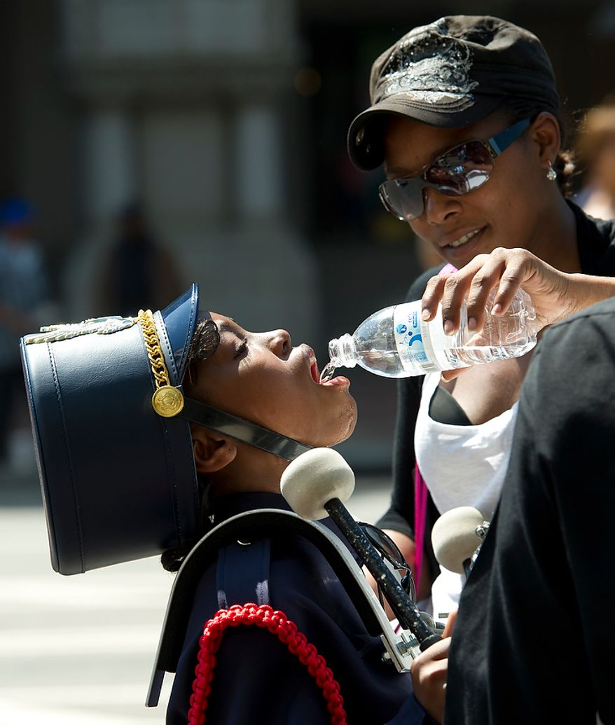 Caprice Casson offers cool water to Dana Treece, 10, a young drummer in the JC Nalle Elementary School band, as they make they way along Pennsylvania Avenue NW during the District of Columbia Emancipation Day 2012 parade in Washington, D.C., Monday, April 16, 2012., celebrating the150th anniversary of the District of Columbia Emancipation Act. 150 ears ago, on April 16, 1862, President Abraham Lincoln signed a bill ending slavery in the District of Columbia. Passage of this law came 8 1/2 months before President Lincoln signed his Emancipation Proclamation. (Rod Lamkey Jr/The Washington Times)