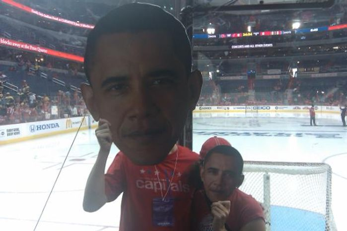 Brian Murphy, 35, and Missy Colombo, 37, show off Barack Obama Heads designed to taunt Tim Thomas before Game 3 of Capitals-Bruins. (Stephen Whyno / The Washington Times)