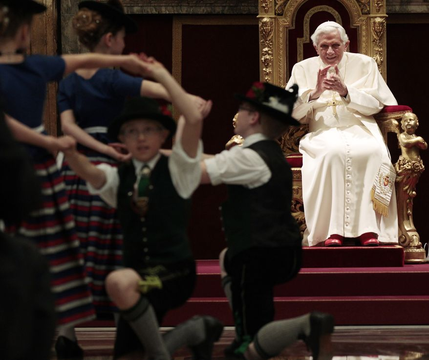 Pope Benedict XVI claps as Bavarian children in traditional garb dance in celebration of the pontiff's 85th birthday anniversary in the Clementine Hall at the Vatican on Monday, April 16, 2012. (AP Photo/Gregorio Borgia, Pool)