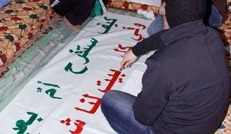 """Anti-regime activists in Syria cover their faces with scarves in the colors of the Syrian revolutionary flag last month as they prepare a protest banner that reads in Arabic, """"How would a mother be happy in the Eid (mother's day) while in each home we have a martyr?"""" With 60 percent of the Arab world's population under 25, protesters say they are working not just for regime change but for the dreams of their generation, on hold for now. (Associated Press)"""