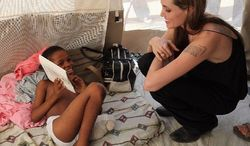A month after Haiti's January 2010 earthquake, Angelina Jolie visits at MSF Hospital in Port-au-Prince with a 10-year-old boy who lost a leg in the quake. The actress is a United Nations special envoy for refugees. (United Nations High Commissioner for Refugees via Associated Press)