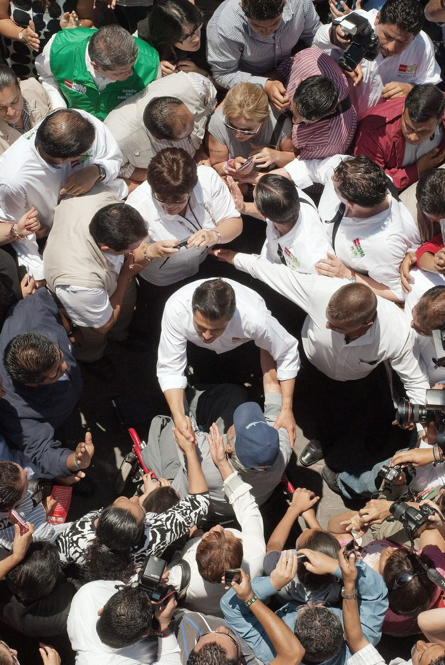 Enrique Pena Nieto, the Institutional Revolutionary Party candidate for president, is mobbed by supporters in Queretaro, Mexico. He has a substantial lead in polls. (Keith Dannemiller/Special to The Washington Times)