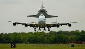 Perched atop a NASA 747, Discovery arrives at Dulles Airport for its final touchdown. After completing 39 missions, the shuttle has a new home at the Smithsonian's Steven F. Udvar-Hazy Center near the airport in Northern Virginia. (Andrew Harnik/The Washington Times)