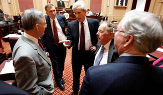 Senate Minority Leader Richard L. Saslaw (center), Fairfax Democrat, talks with Senate Majority Leader Thomas K. Norment Jr. (left), James City Republican, as Sen. Emmett Hanger (second from left), Augusta Republican, and Sen. Charles Colgen (second from right), Prince William Democrat, and Finance Committee Chairman Sen. Walter Stosch, Henrico Republican, listen prior to the debate on the budget conferees' report at the Capitol in Richmond on Tuesday. (Associated Press)