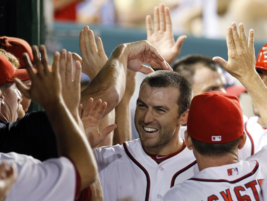 Washington Nationals' Stephen Lombardozzi is congratulated by teammates in the dugout after scoring from second base on a single by Ryan Zimmerman during the sixth inning of a baseball game against the Houston Astros in Washington, Monday, April 16, 2012. The Nationals beat the Astros 6-3. (AP Photo/Ann Heisenfelt)