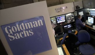 **FILE** A trader works in the Goldman Sachs booth on the floor of the New York Stock Exchange on March 15, 2012. (Associated Press)