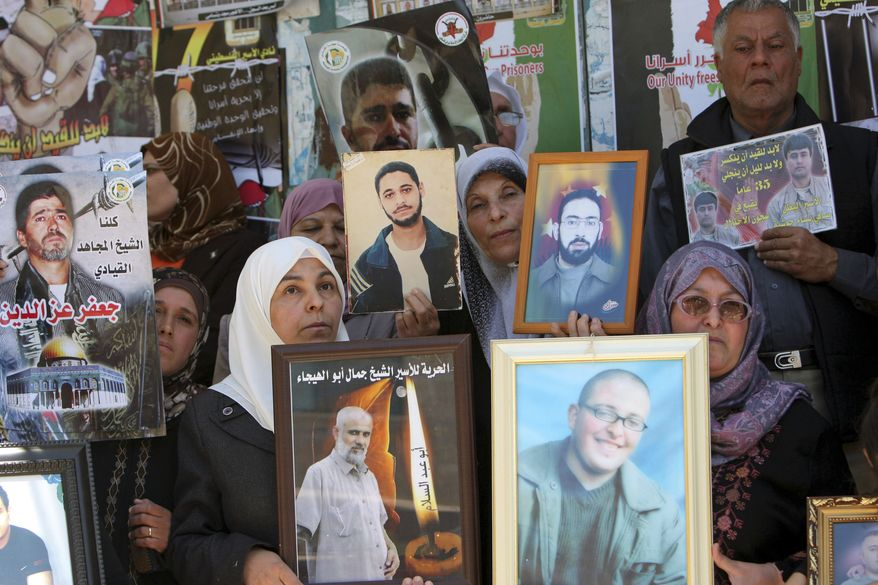 "Demonstrators holding photographs of Palestinians jailed in Israel rally in the West Bank city of Jenin on Tuesday, April 17, 2012, to mark the annual ""Prisoners' Day."" (AP Photo/Mohammed Ballas)"