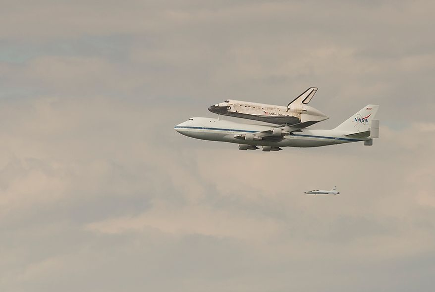 The NASA Space Shuttle Discovery is seen being carried piggyback on a modified Boeing 747, in the skies above Washington, D.C., Tuesday, April 17, 2012, as it makes it's way to the Steven F. Udvar-Hazy Center in Chantilly, Va. (Rod Lamkey Jr/The Washington Times)