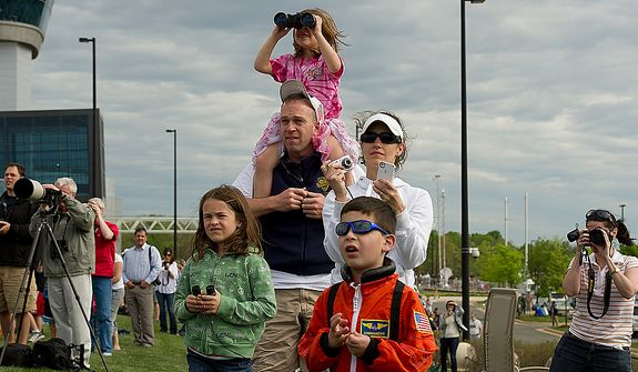 "Ayda Jones, 6, sits on her dad Jeff's shoulders while mom Nicole and sister Ella, 8, watch as the space shuttle Discovery flies towards the Udvar-Hazy Center in Chantilly, Va., on Tuesday, April, 17, 2012. Nicholas Garbini, 5, of Reston, Va., dressed as an astronaut, checks out the scene too. ""I saw the space program start,"" said Jeff Jones, ""so it's kind of sad, but we're very proud of our astronauts."" (Barbara L. Salisbury/The Washington Times)"