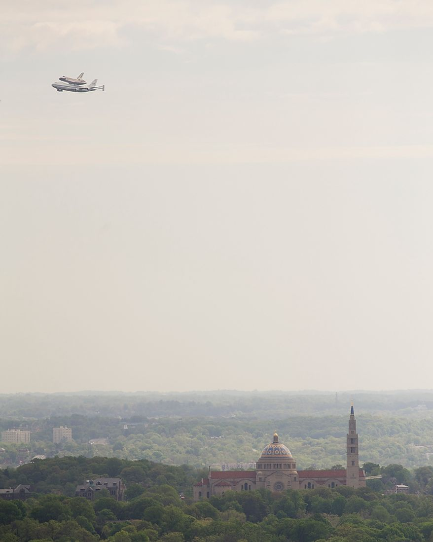 Seen from a tower at the Washington National Cathedral, the NASA Space Shuttle Discovery is seen being carried piggyback on a modified Boeing 747, above the National Shrine of the Immaculate Conception in Washington, D.C.,Tuesday, April 17, 2012, as it makes it's way to the Steven F. Udvar-Hazy Center in Chantilly, Va. (Rod Lamkey Jr/The Washington Times)