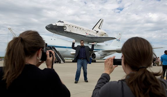 Joan Perry, of Stafor, Va., left, and Christine Rusbarsky, right, of Boston, Mass., photograph Brian Schuetz, center, as he pretends to lift the the space shuttle Discovery after it arrives by 747 carrier aircraft at Washington Dulles International Airport, Chantilly, Va., Tuesday, April 17, 2012. After completing 39 missions and spending 365 days in space, the historic spacecraft will make its final destination at the Steven F. Udvar-Hazy Center, a Smithsonian museum, located in Chantilly, Va., on Thursday, April 19. (Andrew Harnik/The Washington Times)