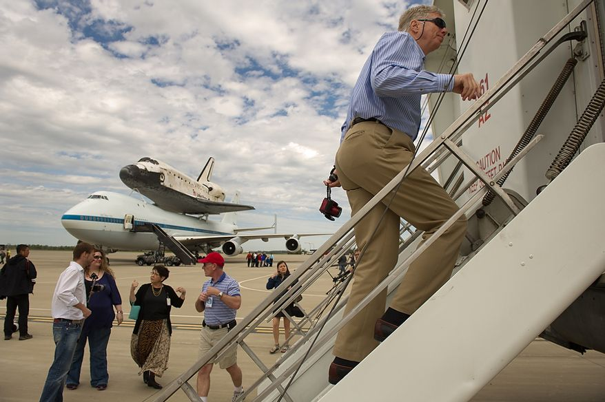 Visitors leave the runway where the space shuttle Discovery arrives by 747 carrier aircraft at Washington Dulles International Airport, Chantilly, Va., Tuesday, April 17, 2012. After completing 39 missions and spending 365 days in space, the historic spacecraft will make its final destination at the Steven F. Udvar-Hazy Center, a Smithsonian museum, located in Chantilly, Va., on Thursday, April 19. (Andrew Harnik/The Washington Times)