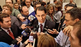 Wisconsin Gov. Scott Walker gives interviews after speaking to the Illinois Chamber of Commerce in Springfield. Mr. Walker says he is using Illinois and its many problems as an argument for keeping him in office with similar problems. The first-term Republican faces a recall election in June. (Associated Press)