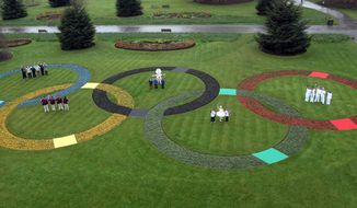 Giant Olympic rings made up of 25,000 flowers are seen April 18, 2012, at Kew Royal Botanic Gardens in London with torchbearers, games makers, London 2012 festival participants and parents of TeamGB athletes, marking 100 days before the start of the London 2012 Olympic Games. The opening ceremony will take place on July 27, 2012. (Associated Press)