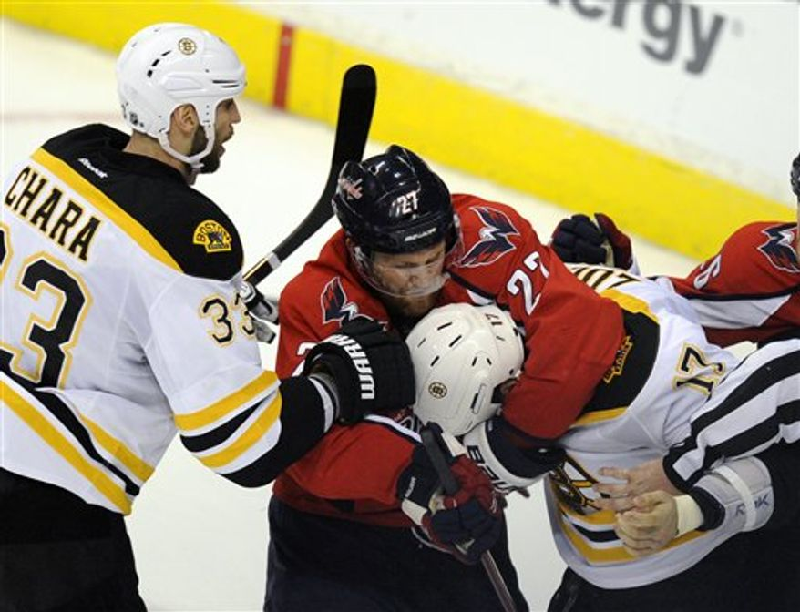 Washington Capitals defenseman Karl Alzner (27) mixes it up with Boston Bruins left wing Milan Lucic (17), next to Bruins' Zdeno Chara (33), of Slovakia, during the third period of Game 3 of an NHL hockey Stanley Cup first-round playoff series, Monday, April 16, 2012, in Washington. The Bruins won 4-3. (AP Photo/Nick Wass)