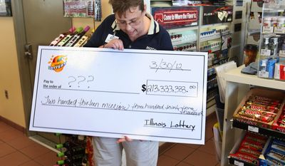 Denise Metzger, manager of the Motomart convenience store in Red Bud, Ill., looks at an oversized check from Illinois Lottery officials on Saturday morning, March 31, 2012, after the officials verified that one of three winning tickets in the largest-ever Mega Millions jackpot had been sold there. (AP Photo/Belleville News-Democrat, Tim Vizer)